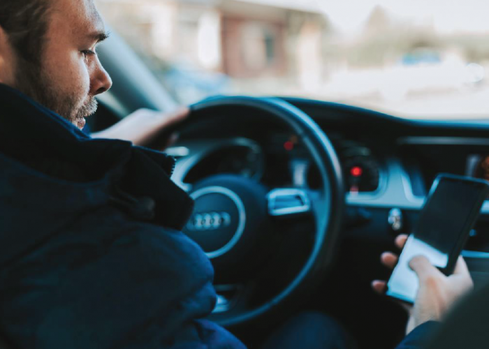 motorista com celular na mão